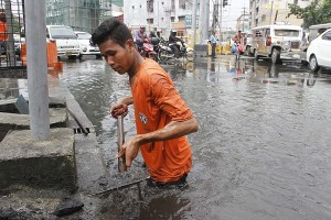 Difficult task: Using a shovel, a Department of Public Works and Highways-National Capital Region (DPWH-NCR) worker unclogs the drainage system along Pedro Gil Street corner Osmena Highway in Manila to ease the floodwater that accumulated in the area on Tuesday (Oct. 11, 2016). (PNA photo by Avito C. Dalan)