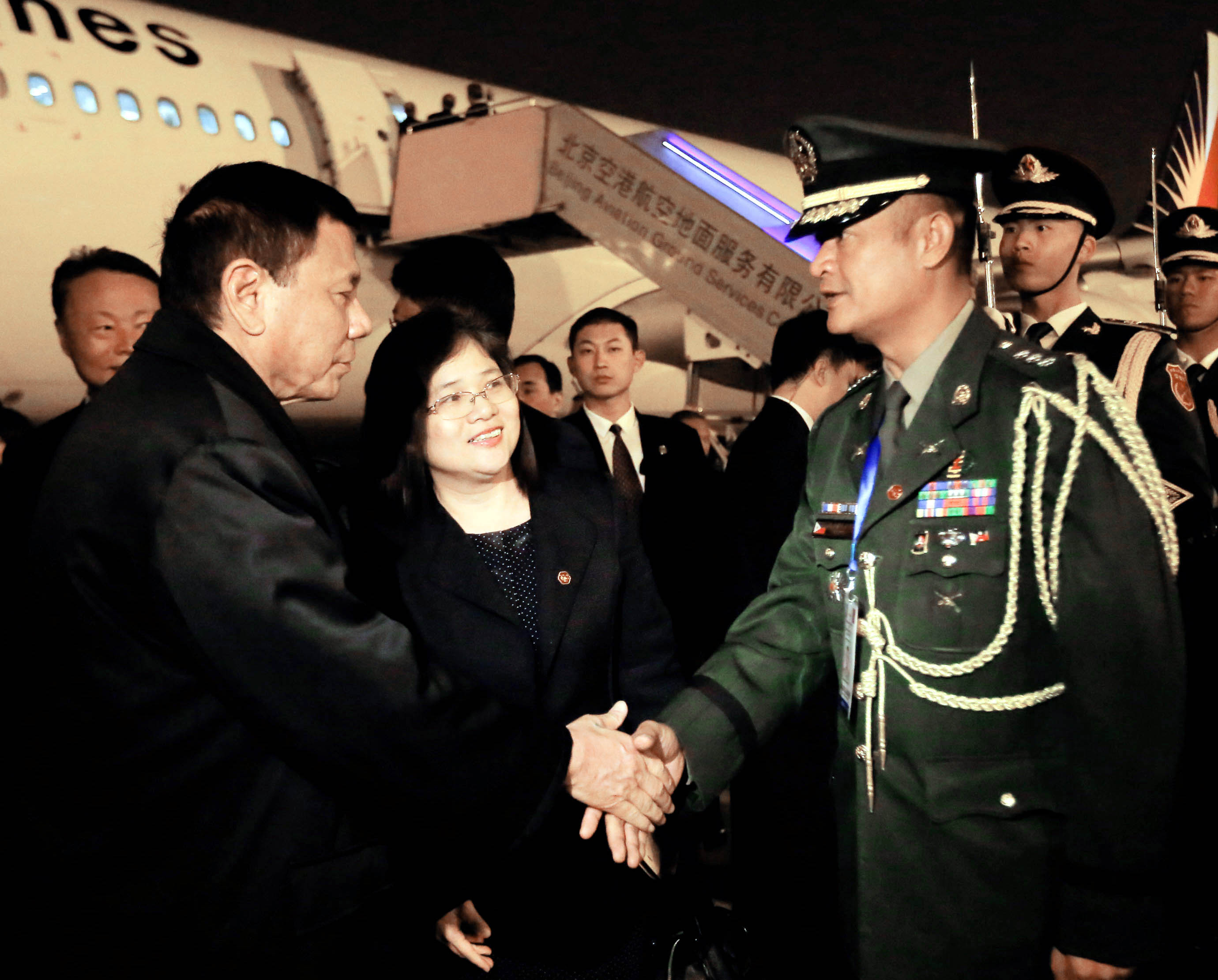President Duterte shakes hands with a Chinese military official: President Rodrigo R. Duterte shakes hands with a Chinese military official upon his arrival at the Beijing Capital International Airport on Monday (Oct. 17, 2016). (PNA photo by Toto Lozano/PPD/PNA)