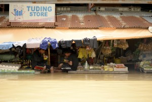 Vendors eat their lunch as they wait for customers at a flooded market in Candaba, Pampanga, north of Manila on Friday. Vast swathes of farmlands inundated by Typhoon Lando in October were flooded again this week due to heavy rains brought by Typhoon Nona.(MNS photo)
