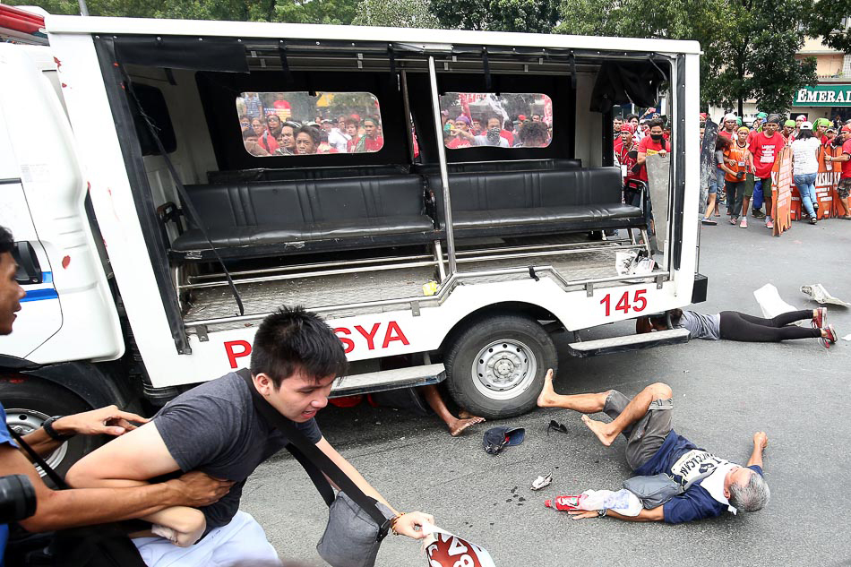 Protesters lie on the ground after being hit by a police van during a rally against the Enhanced Defense Cooperation Agreement (EDCA) in front of the US embassy in Manila on Wednesday. A Philippine police van rammed and ran over the protesters. (MNS photo)