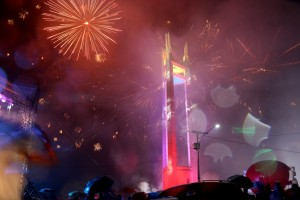 People watch the fireworks display to welcome the new year at the Quezon Memorial Circle in Quezon City on Friday despite the rain. Fireworks in many neighborhoods were toned down compared to previous years because of a selective ban on firecrackers.(MNS photo)