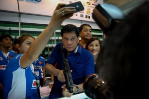 Davao City mayor Rodrigo Duterte holds a sub-machinegun as admirers take a selfie with him during the 23rd Defense and Sporting Arms Show at SM Megamall on Wednesday. In his speech, Duterte again espoused his idea of governance despite being non-committal to running for the presidency. (MNS photo)
