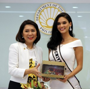 """Miss Universe Pia Alonzo-Wurtzbach visits the new Department of Tourism Office: Miss Universe Pia Alonzo-Wurtzbach receives a token of appreciation from Department of Tourism (DOT) Secretary Wanda Corazon Teo during the former's visit at the new DOT Headquarters along Sen. Gil Puyat Ave. in Makati City on Monday (July 18, 2016). In a press conference after their meeting, Secretary Teo said she is grateful for the full support the reigning Miss Universe is giving to DOT's efforts to host the upcoming Miss Universe contest in the country. """"We are really hopeful that President Rodrigo R. Duterte will grant our request, especially now that this undertaking would practically entail no expense on the part of government. More importantly, it would give a big boost to businesses and livelihood of millions of people, in line with our 'shared tourism' program,"""" the DOT Chief said. (PNA photo by Jess M. Escaros Jr.)"""