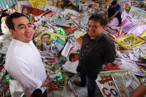Commission on Elections Chairman Andy Bautista (left) and Metropolitan Manila Development Authority Chairman Atty. Emerson Carlos (right) inspect confiscated campaign materials in Santolan, Quezon City on Friday. The Comelec encouraged citizens to submit photos of candidates who use unlawful campaign materials.(MNS photo)