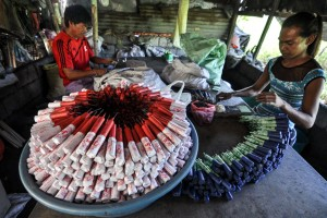 Workers wrap fireworks at a makeshift factory in Bocaue, Bulacan. Production of fireworks has stepped up in anticipation of New Year celebrations despite the Department of Health advisory to avoid the use of firecrackers as numerous incidents have led to scores of injuries.(MNS photo)