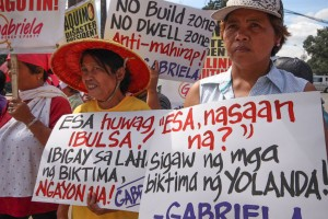 Members of the women's group GABRIELA hold a protest outside the DSWD headquarters in Quezon City on Friday, to mark the 2nd year commemoration of Typhoon Yolanda. The group pushed for the immediate release of the Emergency Shelter Assistance to help victims with their recovery.(MNS photo)