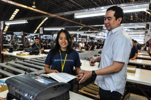 Commission on Election Chairman Andres Bautista demonstrates the function of a vote-counting machine (VCM), which will be used for the May 9 national and local elections, at a warehouse in Sta. Rosa, Laguna, Thursday. The machines are currently undergoing Hardware Acceptance Test (HAT).(MNS photo)