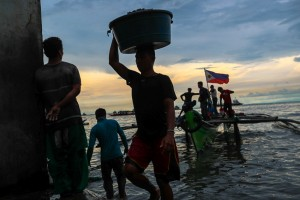 Workers haul their catch of clams and mussels in the late afternoon at the Navotas fish port in Manila on Tuesday. President Duterte is set to discuss rights and access of Filipino fishermen to the disputed West Philippine Sea during his visit to China on October 19-21.(MNS photo)